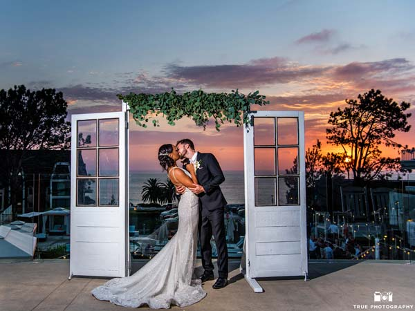 Bride and groom kissing under the sunset.